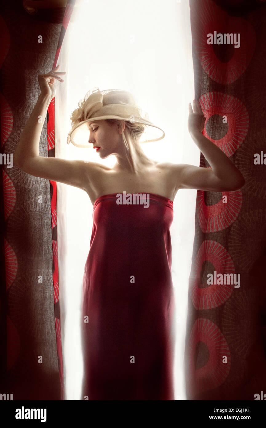 junge schöne Model posiert mit roten Vorhängen Stockfoto