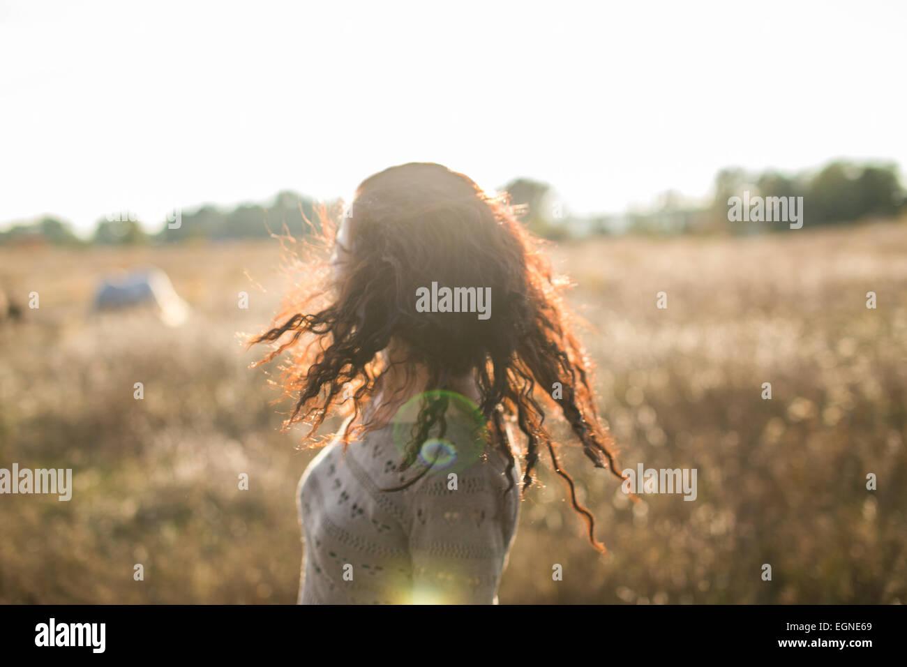 Junges Mädchen kopfschüttelnd auf einem Spaziergang im Feld bei Sonnenuntergang Stockbild