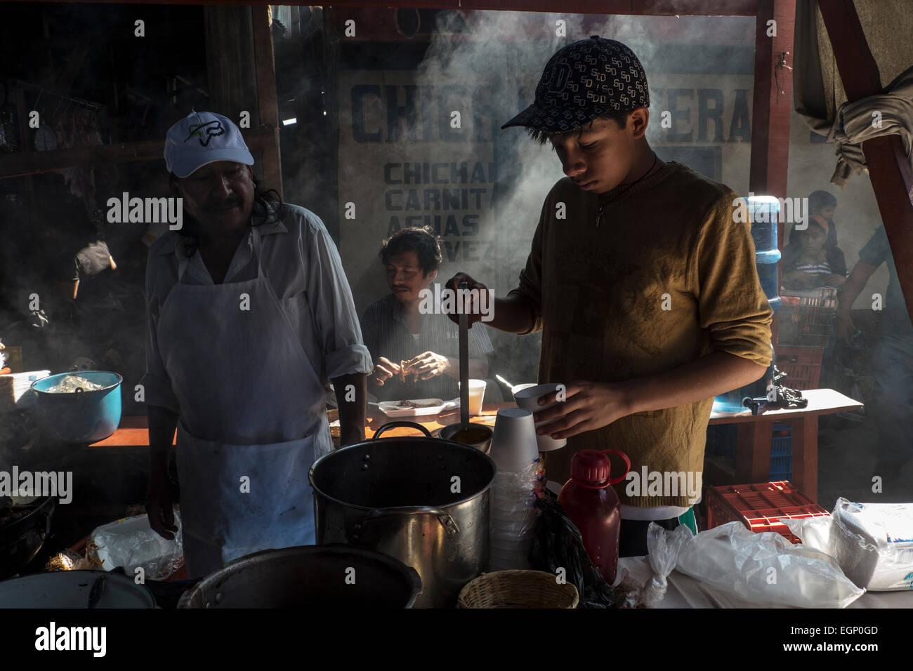 Junge ergießt sich ein heißes Getränk in einem einheimischen Restaurant in Chichicastenango Markt Stockbild