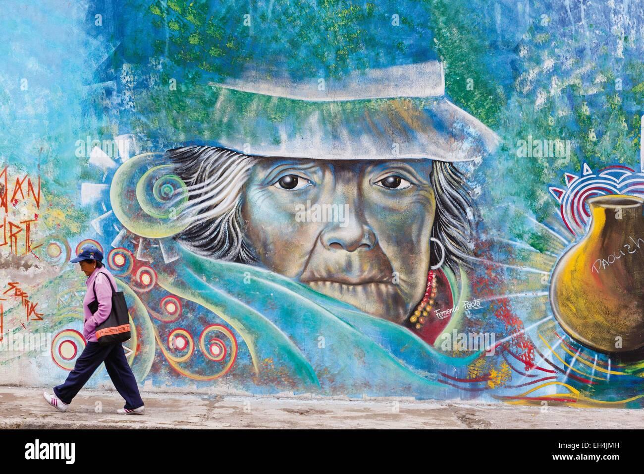 Ecuador, Imbabura, Atuntaqui, ecuadorianischen Beschäftigte moderne Frau vor einer Wand Graffiti zeigt eine Stockbild