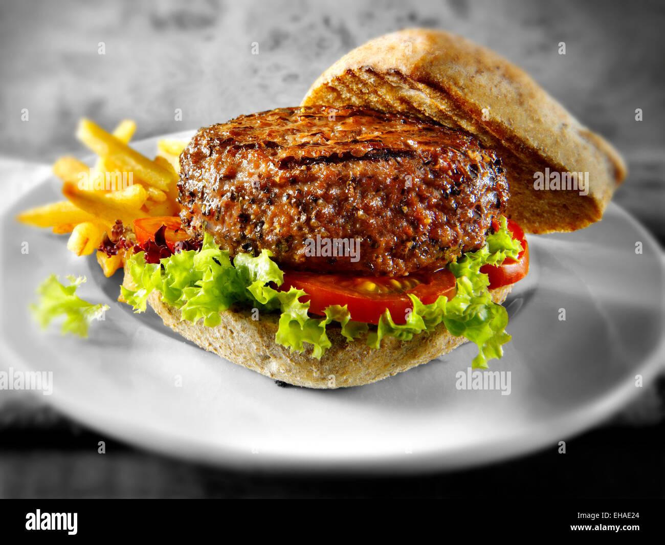 Rindfleisch-Burger mit Salat in einem Vollkorn Brot Brötchen und Pommes frites Stockbild