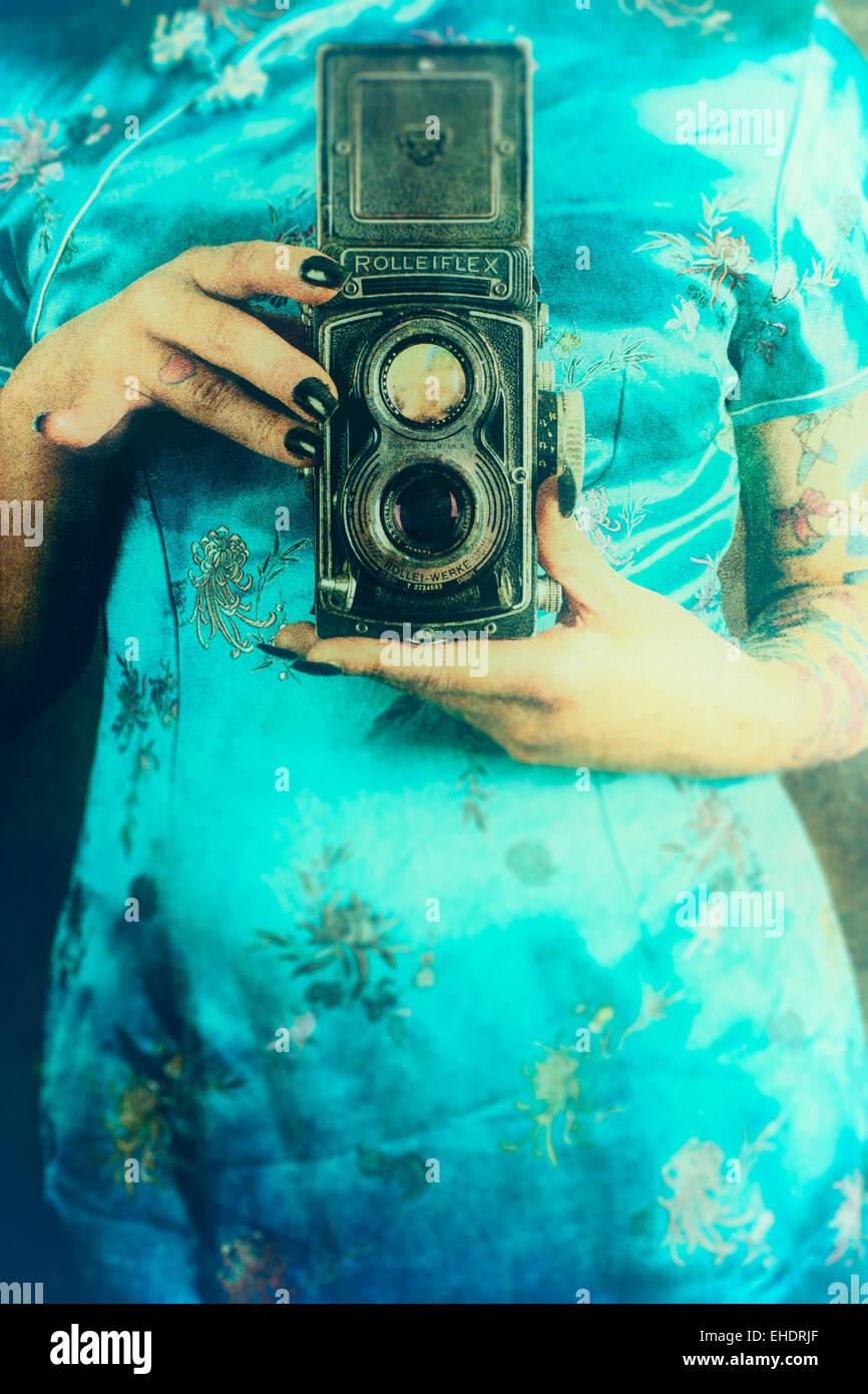 Frau trägt ein chinesisches Kleid eine Vintage Rolleiflex Kamera halten Stockfoto
