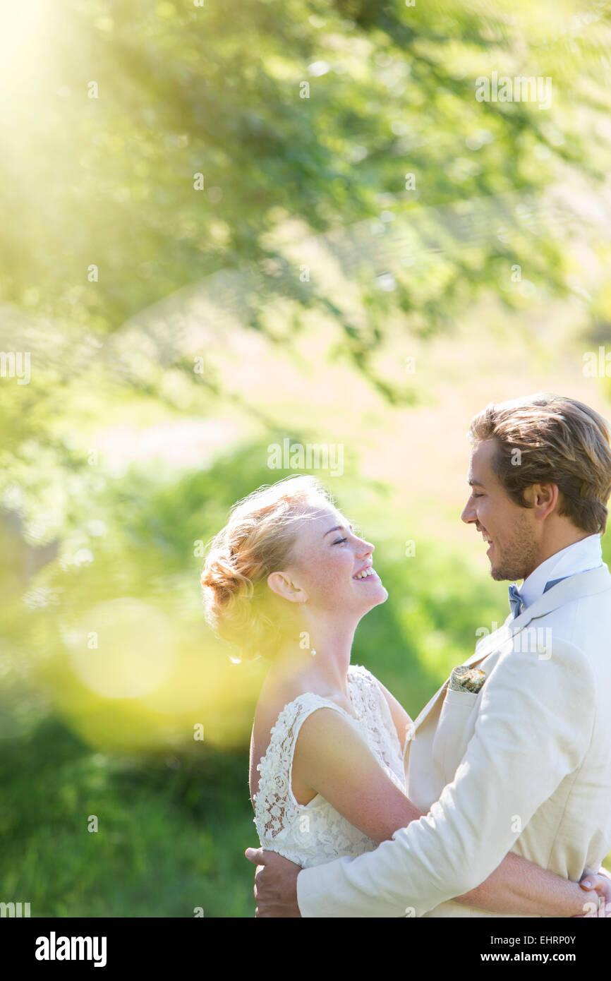Junge, lächelnde paar umarmt im heimischen Garten Stockbild