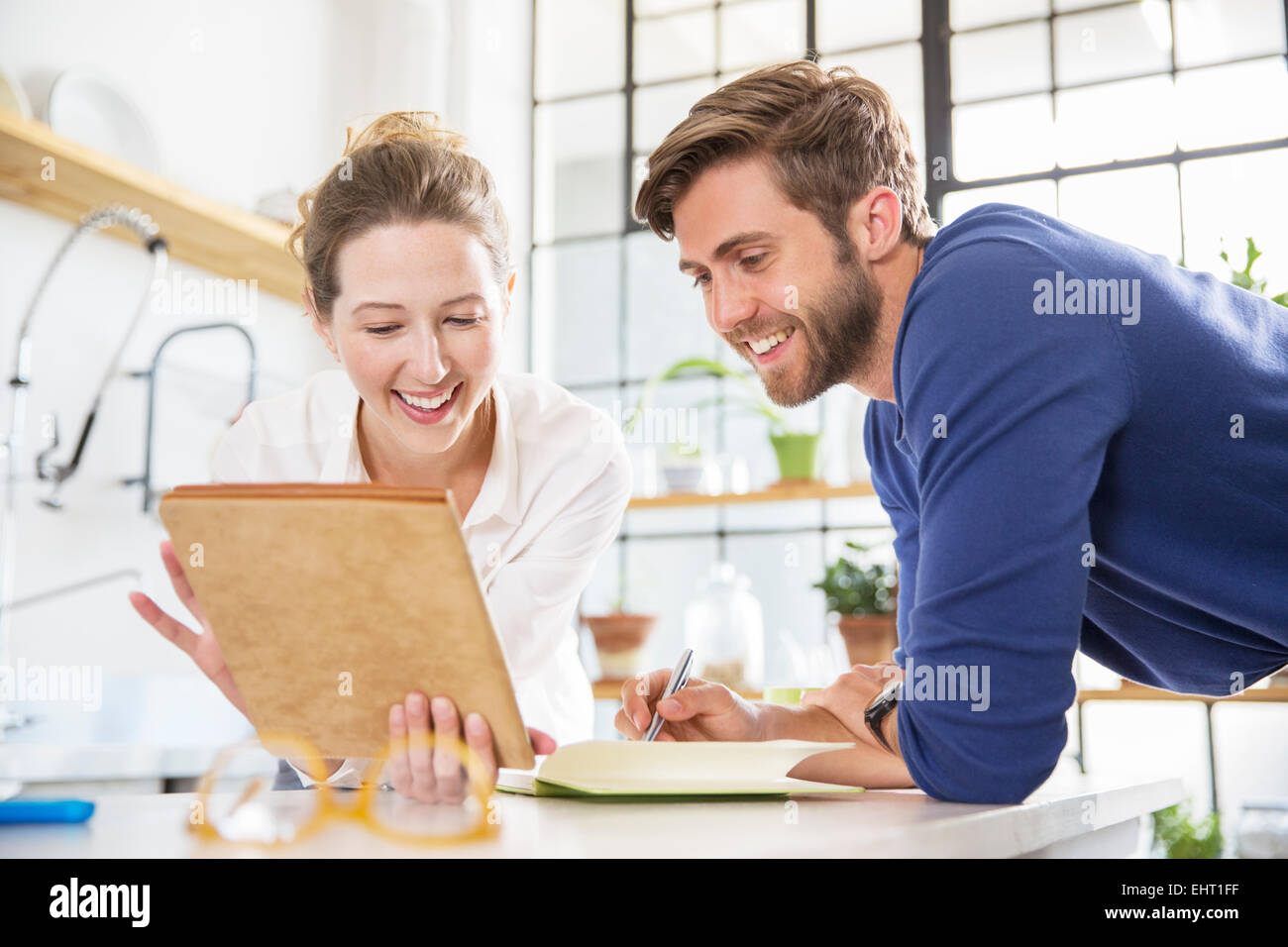 Zwei Jugendliche auf der Suche auf Dokumente in der heimischen Küche Stockbild