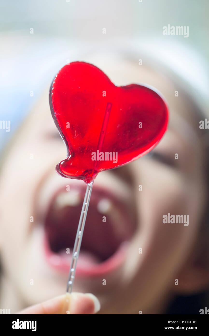 Des Mädchens offenem Mund und herzförmigen lollipop Stockbild