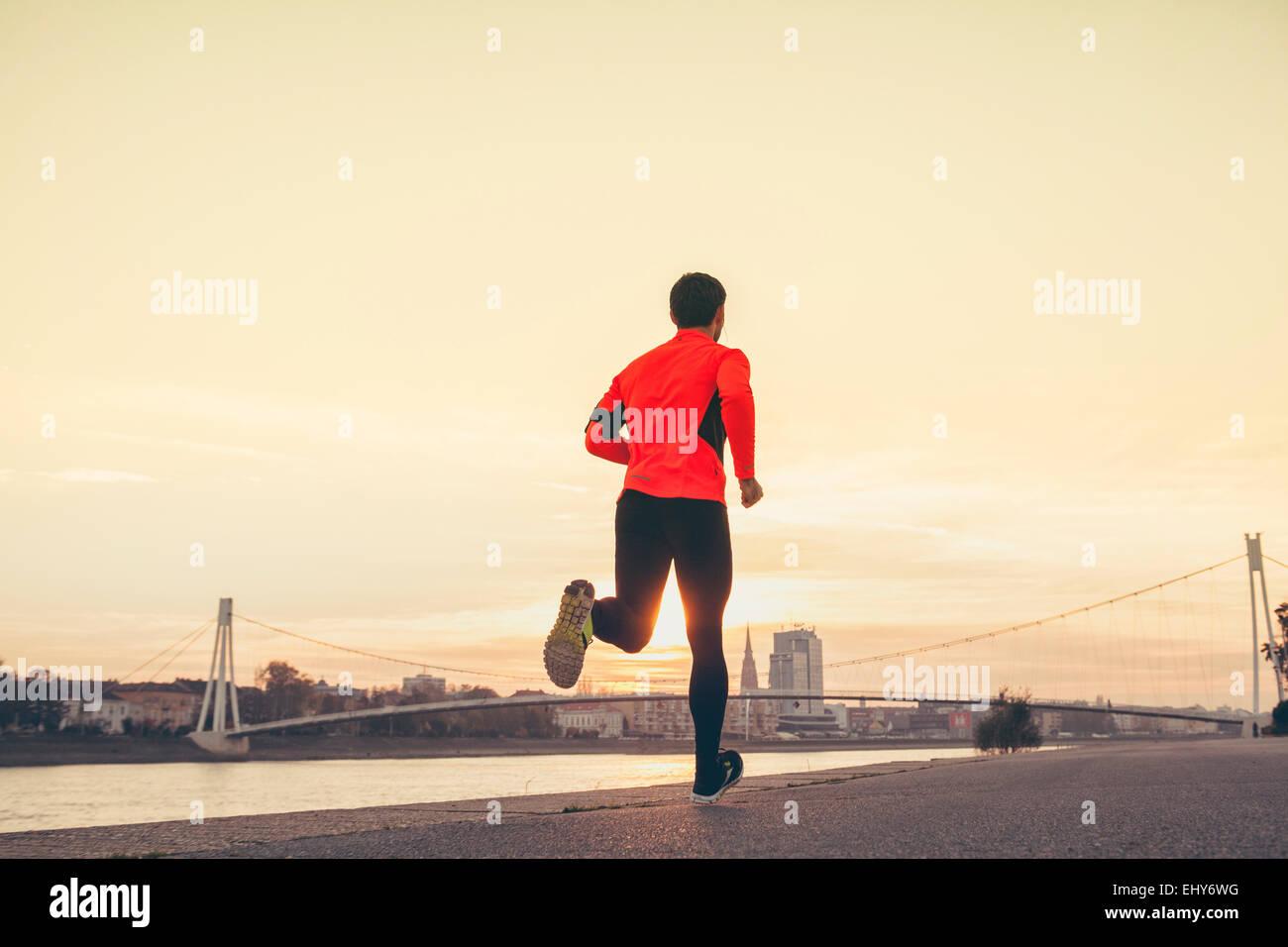 Mann Joggen am Wasser gegen die Skyline der Stadt Stockbild
