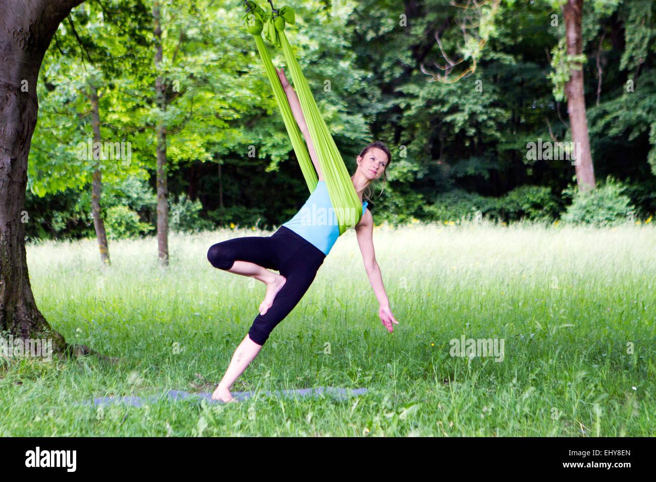 Junge Frau tut stretching-Übungen mit Gummiband, München, Bayern, Deutschland Stockbild