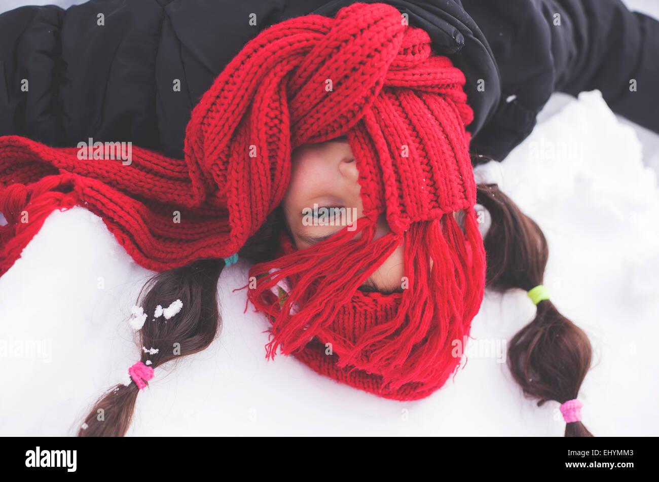 Mädchen mit rotem Schal bedeckte Gesicht im Schnee liegen Stockbild