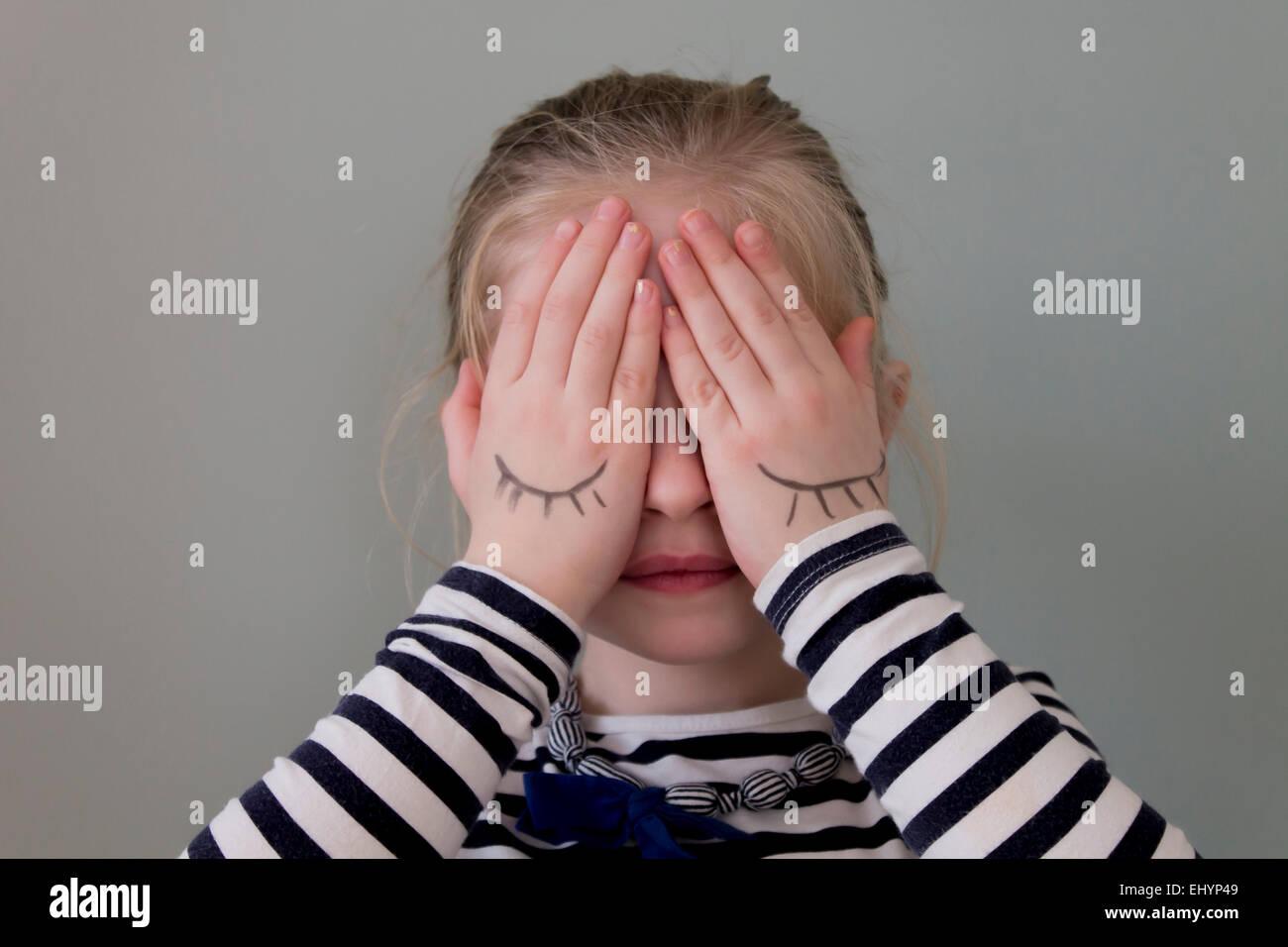 Mädchen für ihre Augen mit Händen, die Augen auf sie gezeichnet haben Stockbild