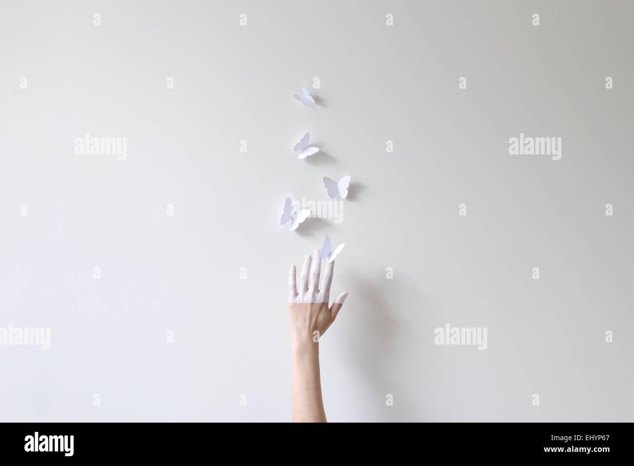 Eine Hand, die Hälfte in weißen Griff nach Papier Schmetterlinge gegen die weiße Wand gemalt Stockbild