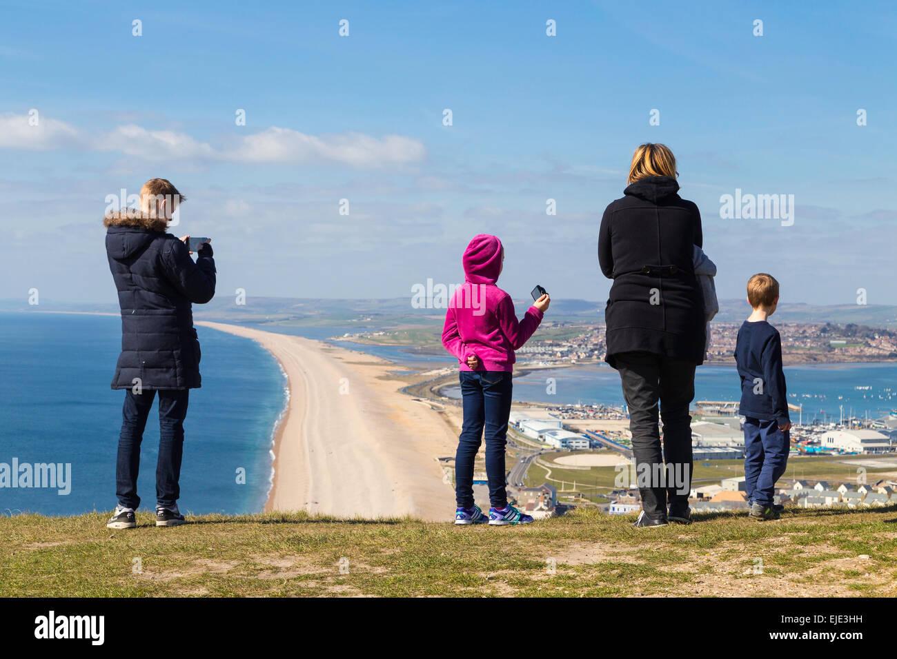 Eine deutsche Familie sind fotografieren und genießen den Blick auf Portland Harbour und Chesil Beach an einem Stockbild