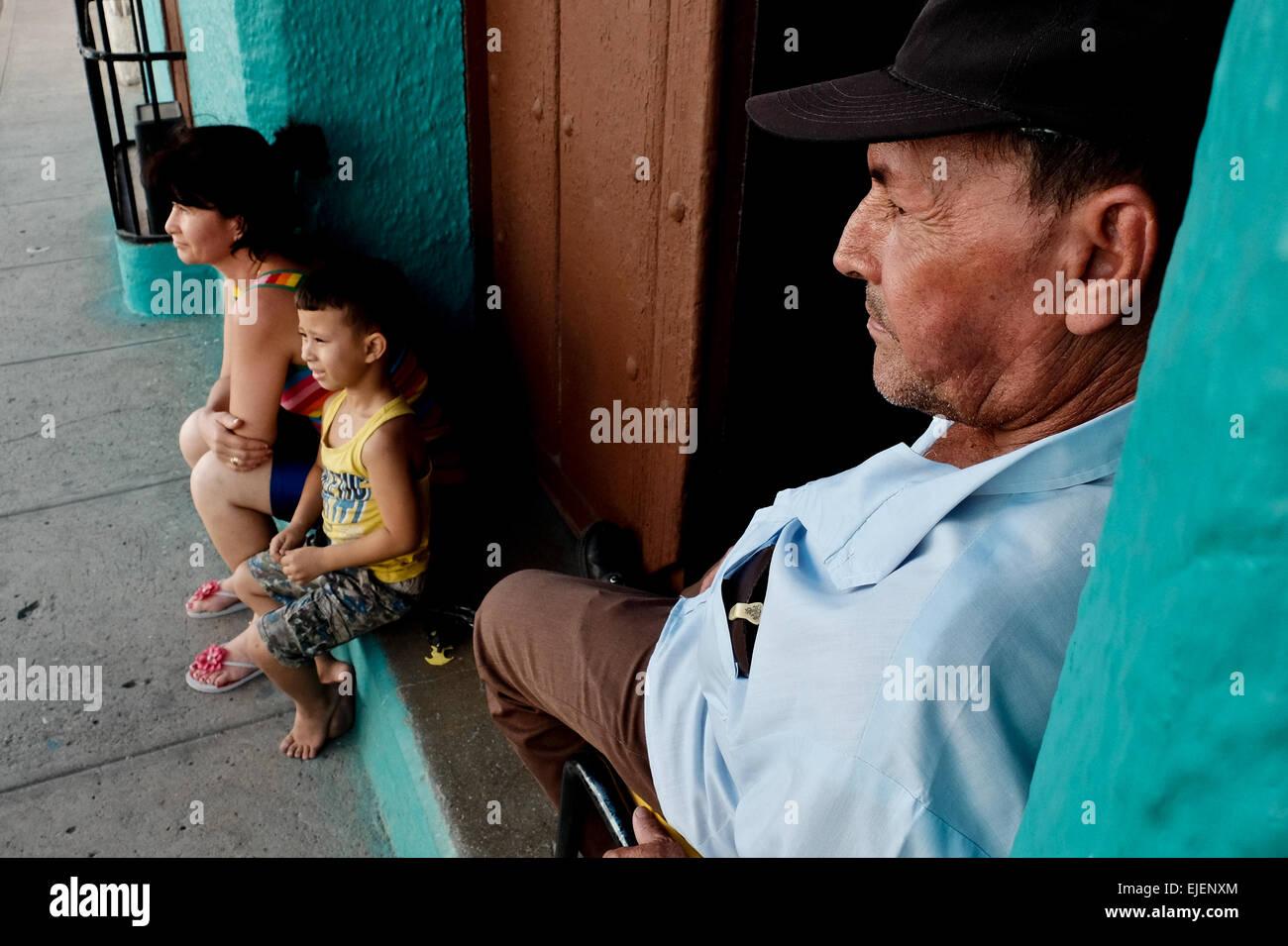 Ein Mann wacht über seine Familie vor der Haustür zu ihrem Haus in der 500 Jahre alten Stadt Sancti Spíritus, Kuba. Stockfoto