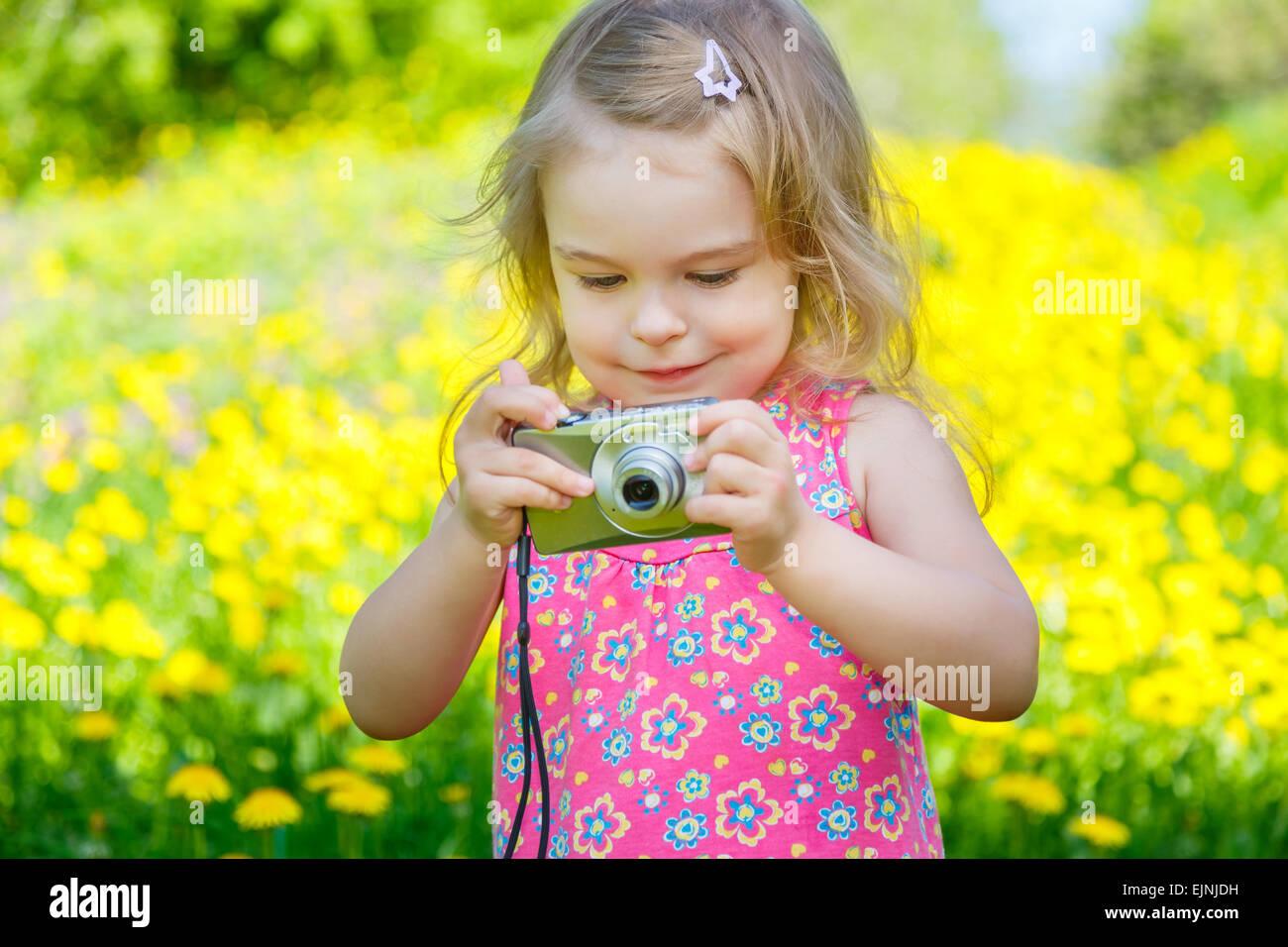 Kleines Mädchen fotografieren auf einer Wiese Stockbild