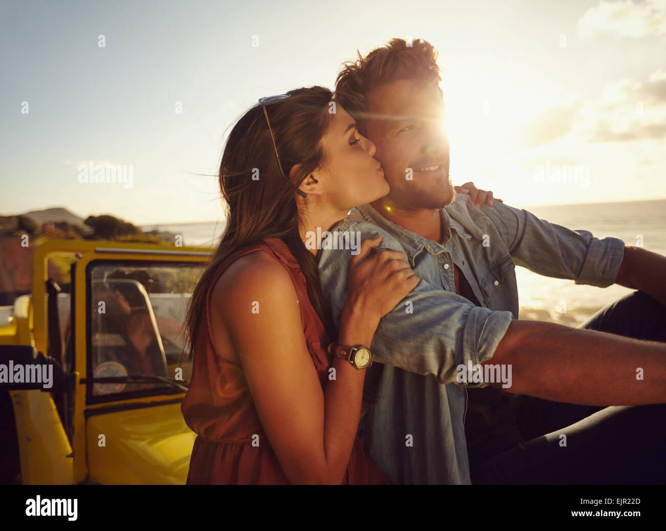 Romantische junges Paar sitzt auf der Motorhaube ihres Autos auf einem Roadtrip. Schöne junge Frau küssen Stockbild