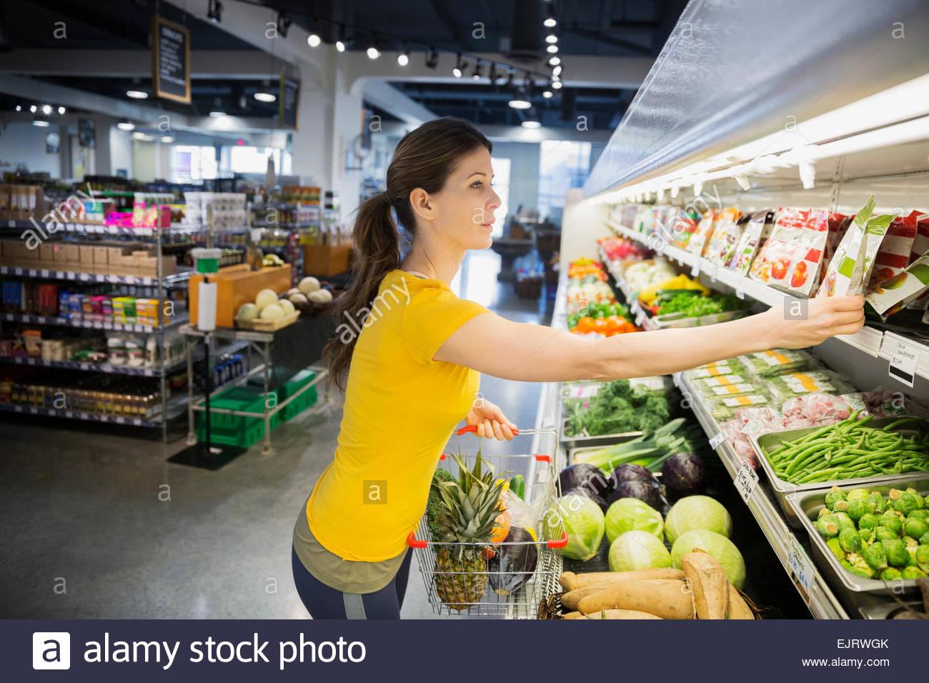 Frau für Produkte im Supermarkt einkaufen Stockbild