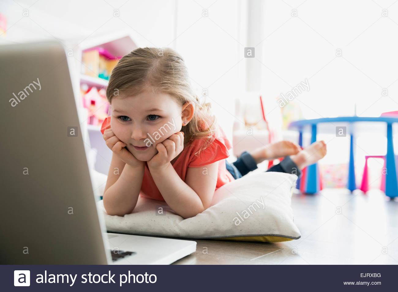 Mädchen mit Laptop im Stock mit Kissen Stockbild