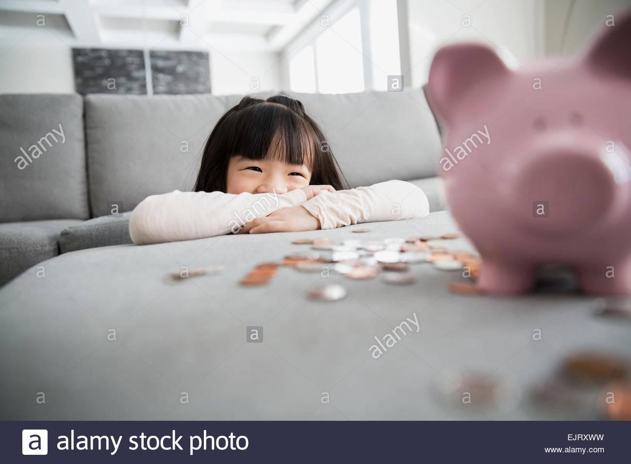 Lächelndes Mädchen mit Sparschwein und Münzen Stockbild