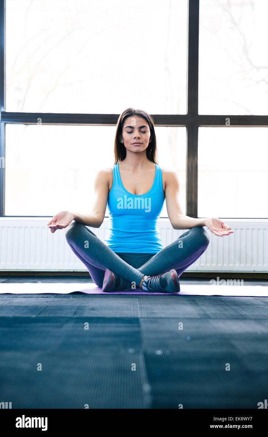 Schöne Frau auf Yoga-Matte sitzen und meditieren in Turnhalle Stockbild