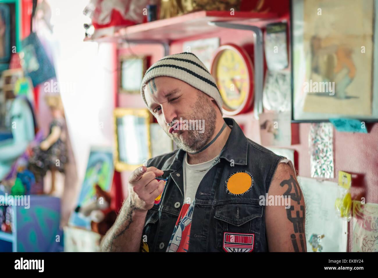 Porträt von männlichen Punk-Ladenbesitzer Zwinkern in Vintage Spielzeug-shop Stockbild
