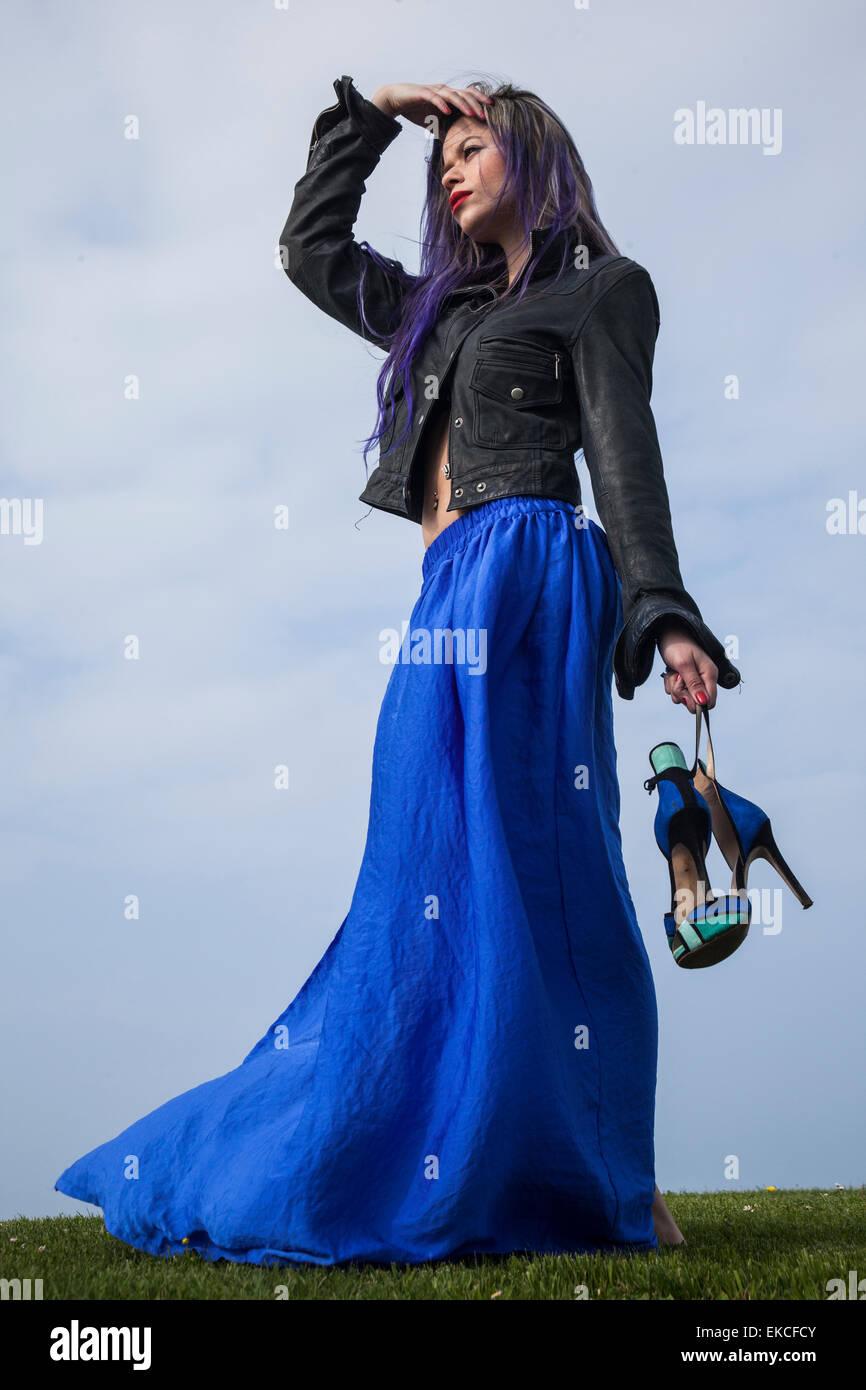 Junge Frau hält ihre Schuhe während der Suche in Ferne Stockbild