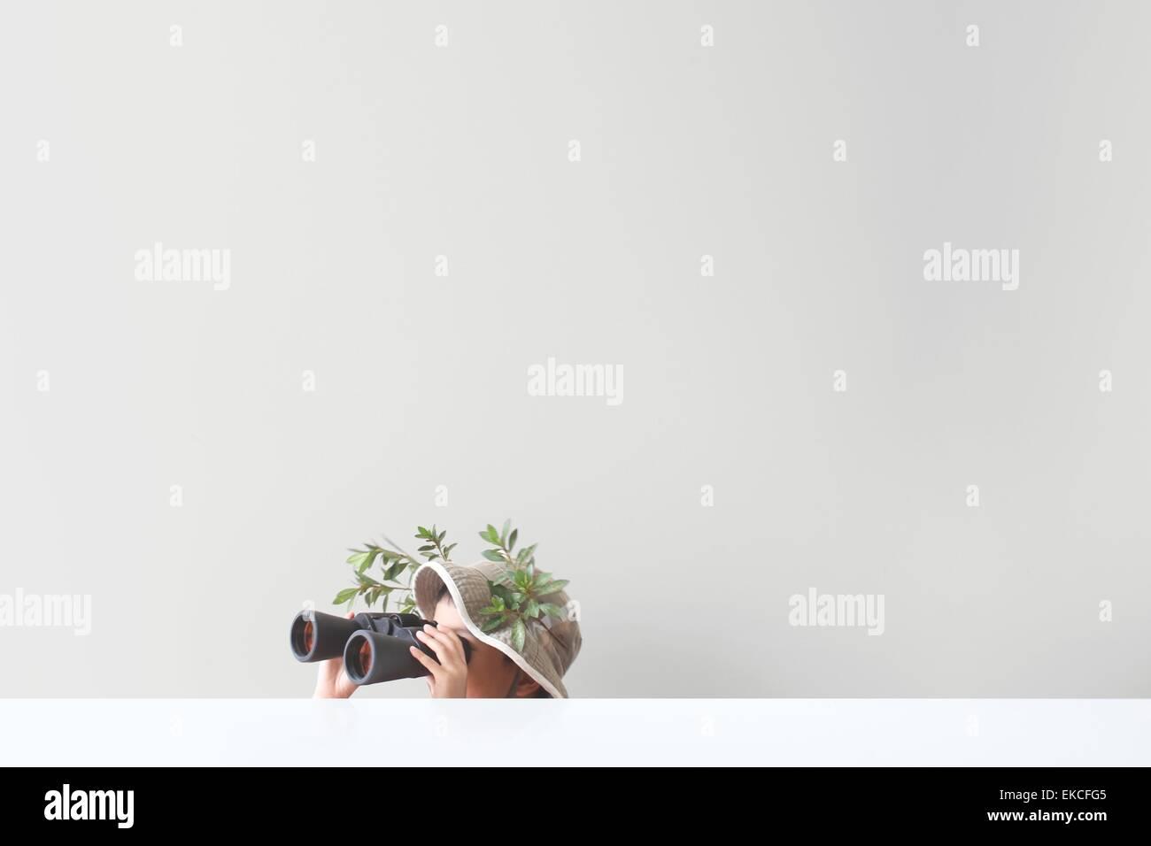 Junge Blick durch ein Fernglas mit einigen Blättern und Ästen auf seinen Safari Hut stecken Stockbild