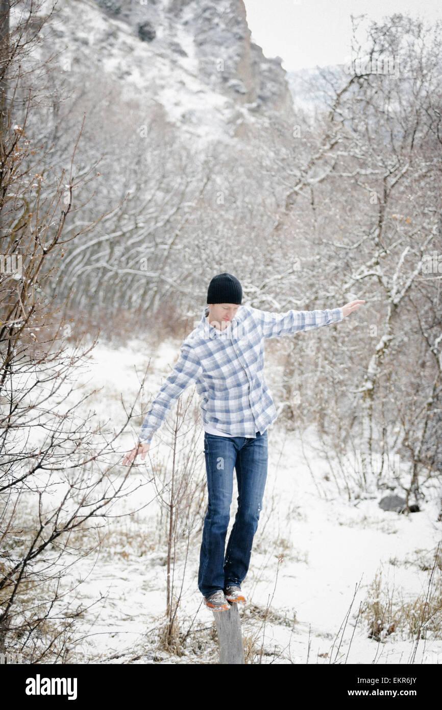 Ein Mann in den Bergen im Winter, balancieren auf einem Holzpfosten in den Wäldern. Stockbild