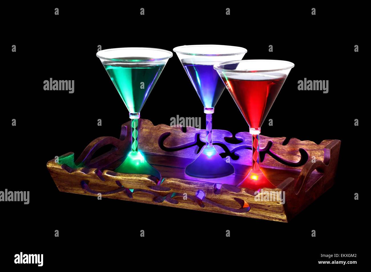 eine dekorativ geschnitzte schale mit drei cocktail gl ser von denen jede durch ein led licht. Black Bedroom Furniture Sets. Home Design Ideas