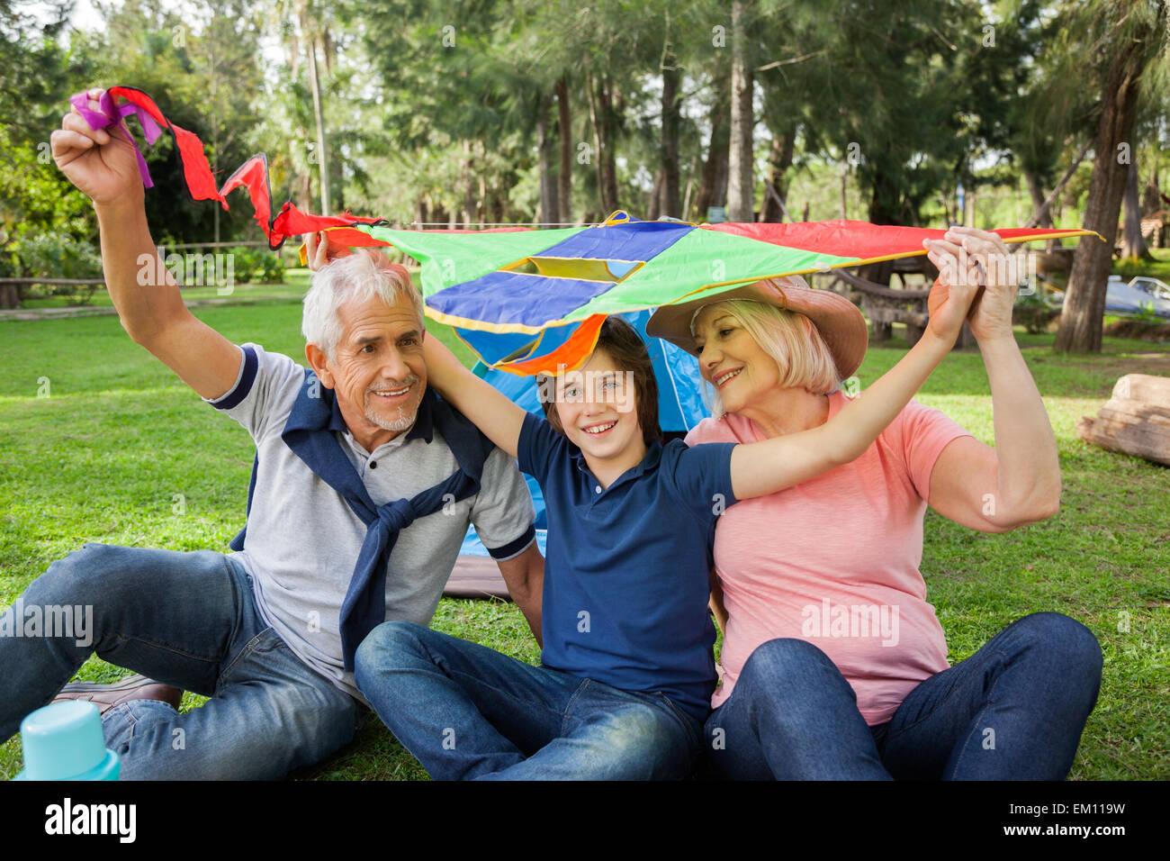 Fröhlicher Junge mit Großeltern halten Kite auf Campingplatz Stockbild