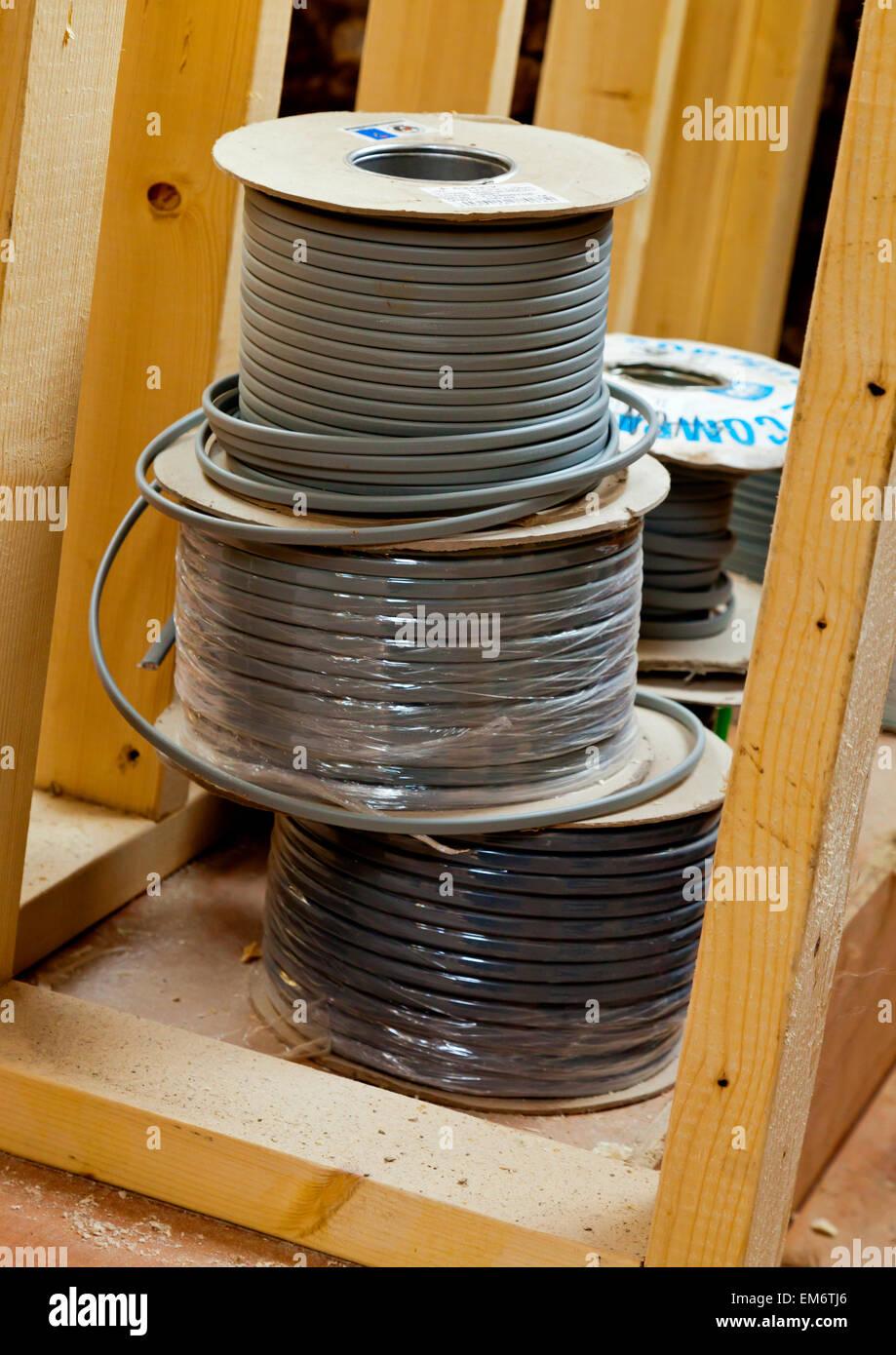 Spulen Elektrokabel vom Elektriker auf der Baustelle installiert werden Stockbild