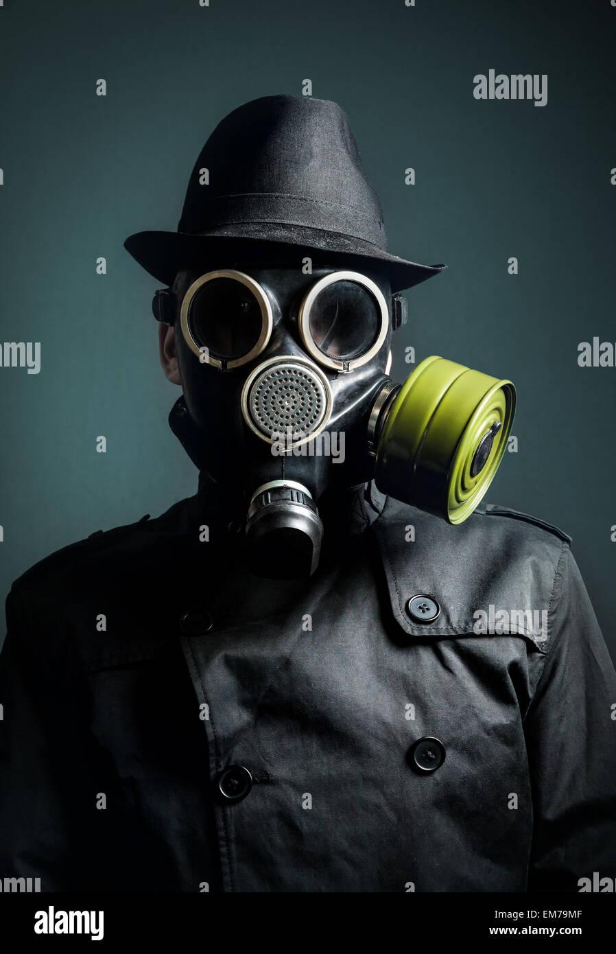 Mann in der Gasmaske, Regenmantel und schwarzen Hut auf dunklem Hintergrund Stockbild