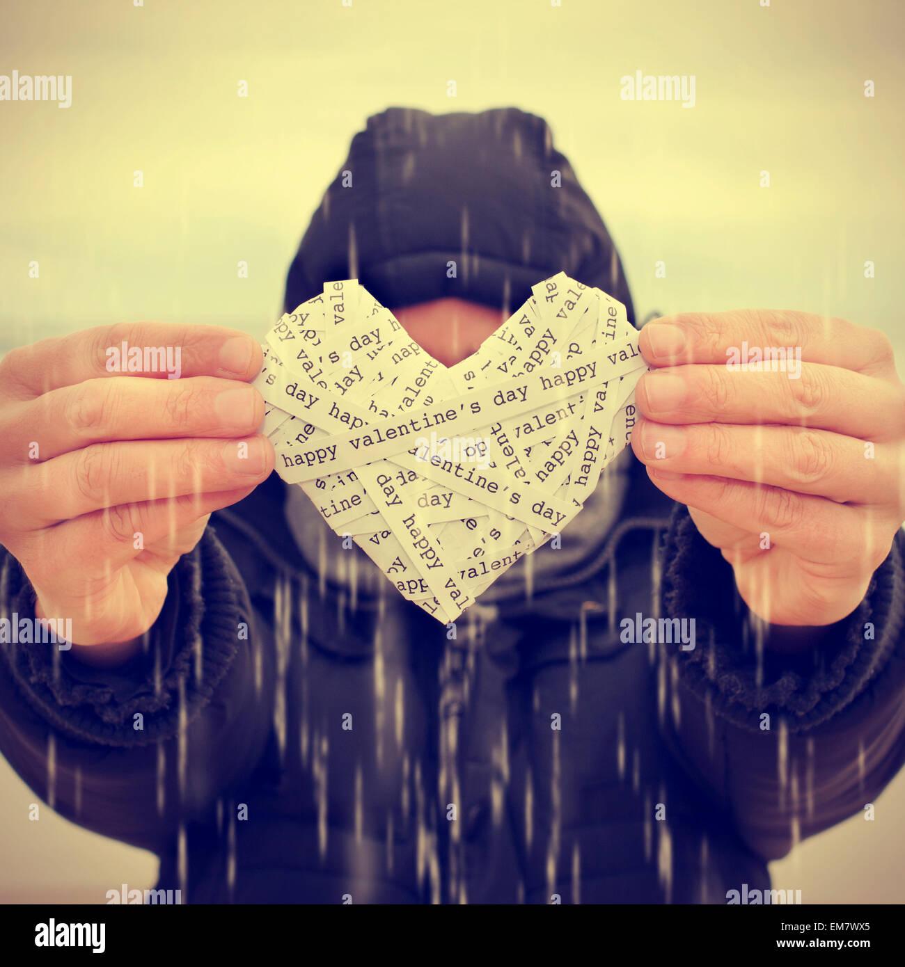 ein junger Mann unter dem Regen zeigt ein Herz mit Papierstreifen mit dem Text happy Valentines Day mit einem Filtereffekt Stockbild