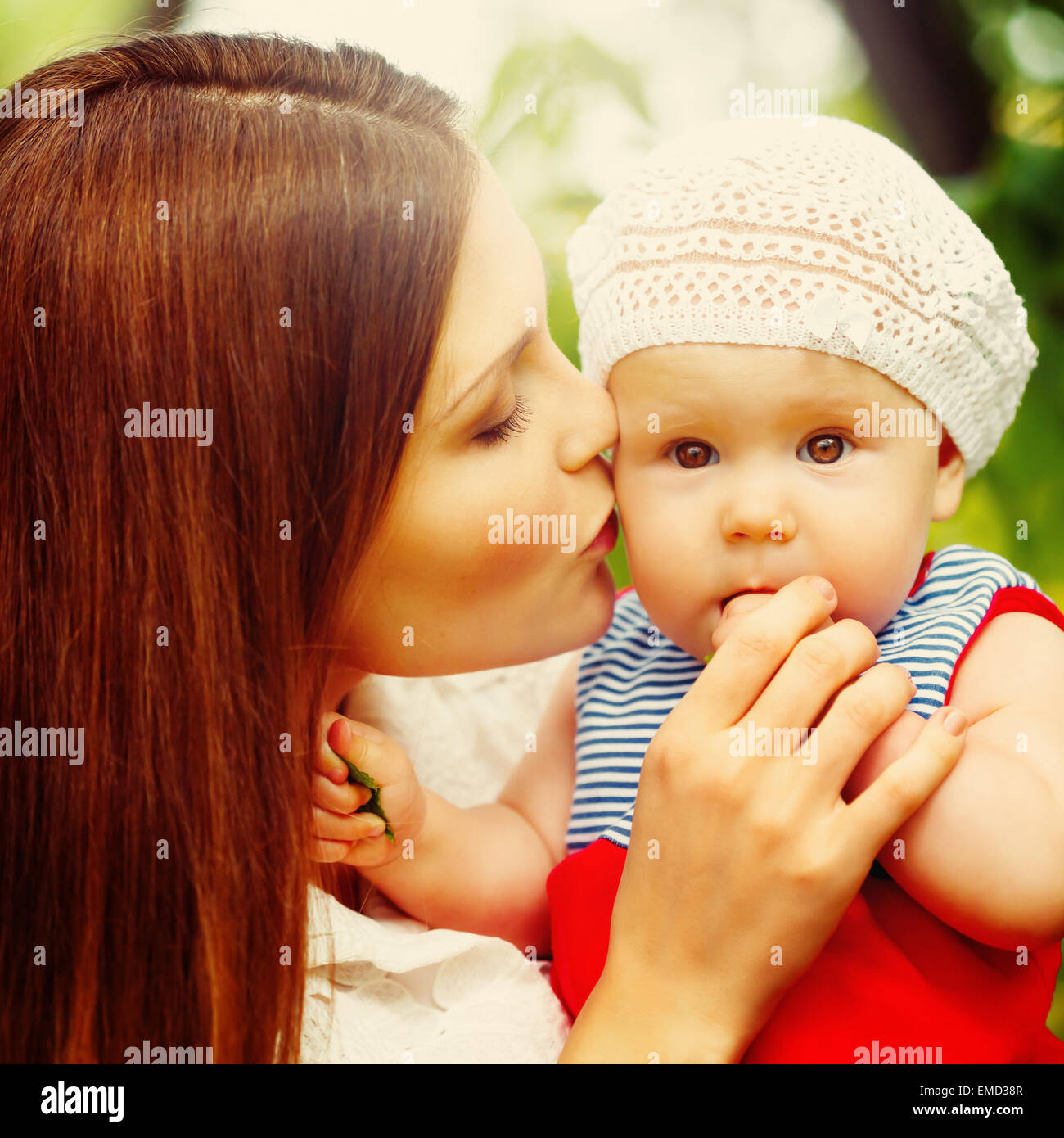 Überrascht Kleinkind Baby Mädchen sitzen auf Mamas Hände, Blick in die Kamera. Mutter das Kind küssen. Stockbild