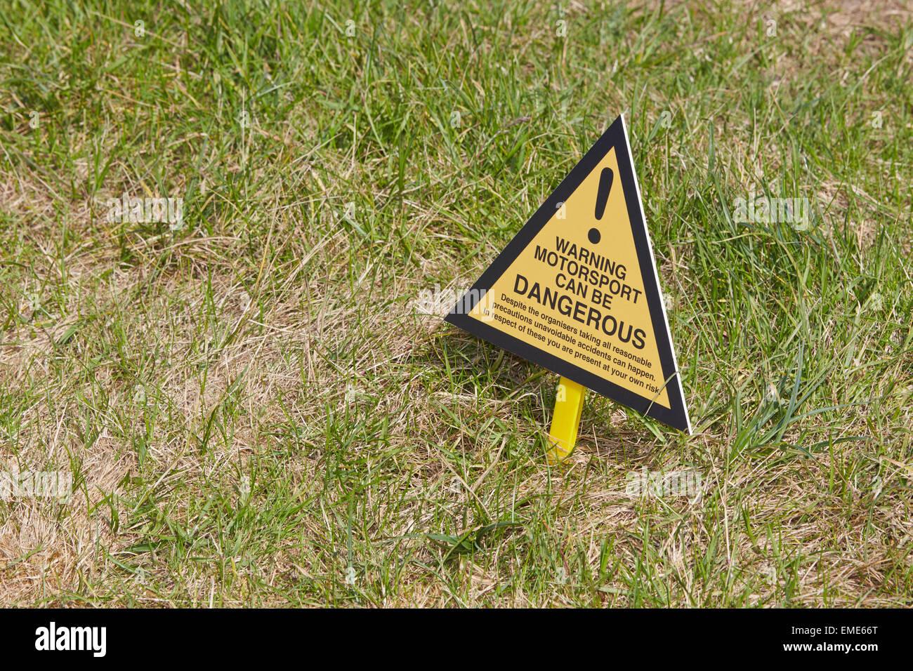 Schild mit der Aufschrift Warnung Motorsport Ican gefährlich werden auf dem Santa Pod Raceway Stockbild