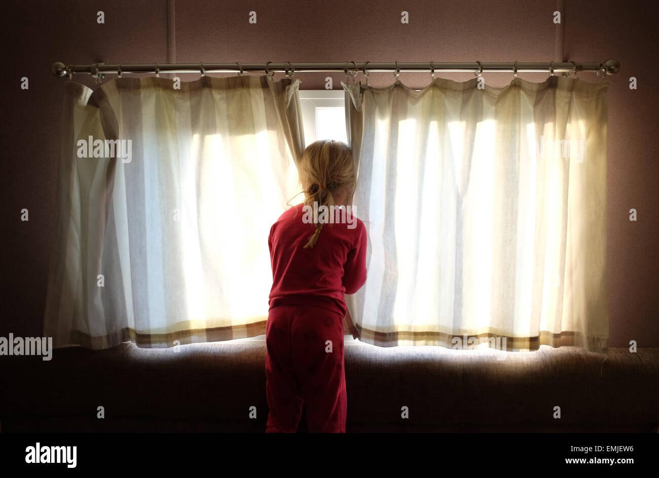 Ein verschlafenes junges Mädchen im Schlafanzug öffnet die Vorhänge, Blick aus dem Fenster zu Beginn Stockbild