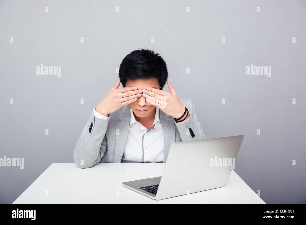 Jungunternehmer am Tisch sitzen und seine Augen auf grauem Hintergrund bedecken Stockbild