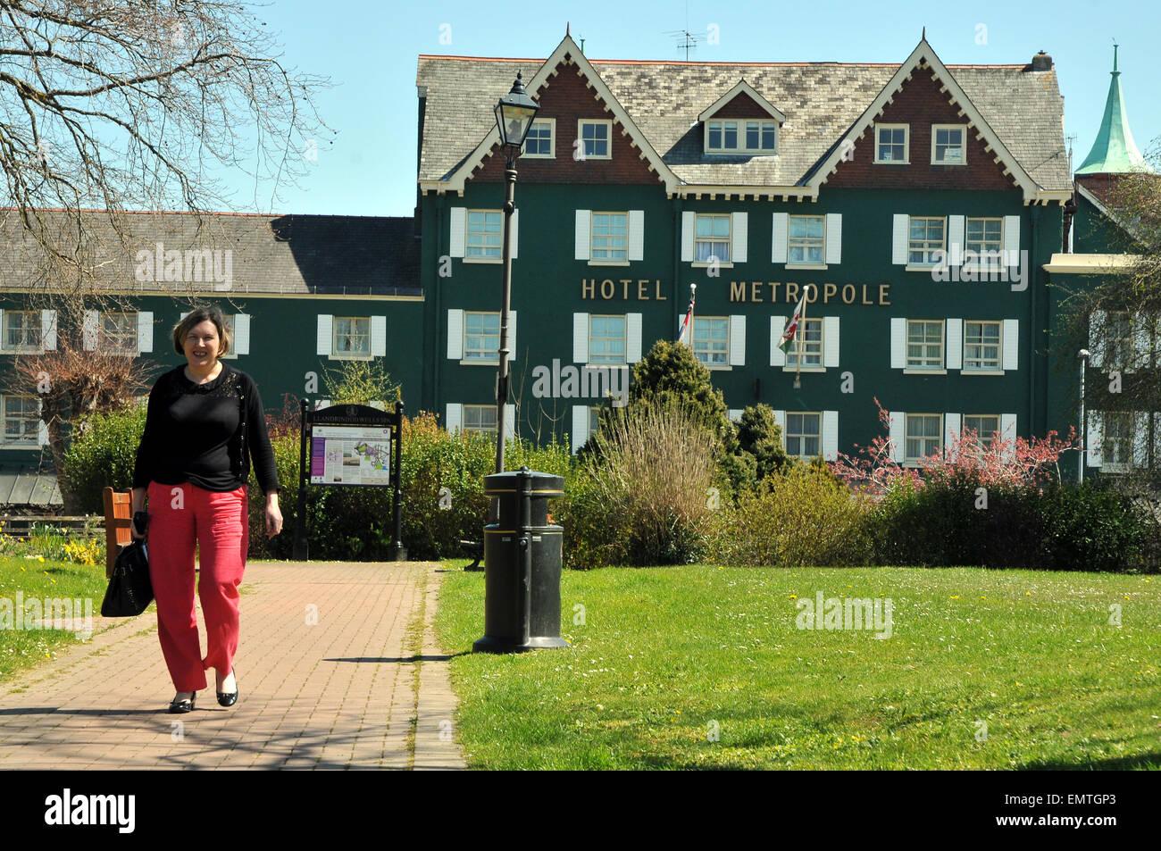 Eine Frau, die zu Fuß zur Arbeit vor dem Hotel Metropole in Llandrindod Wells Stockbild