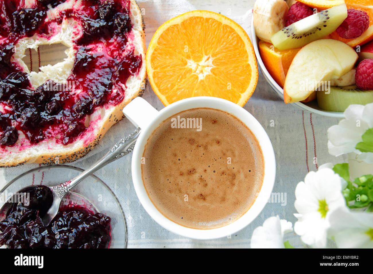 Frühstück mit Brot mit Johannisbeeren Marmelade, Kaffee und Obst Stockbild