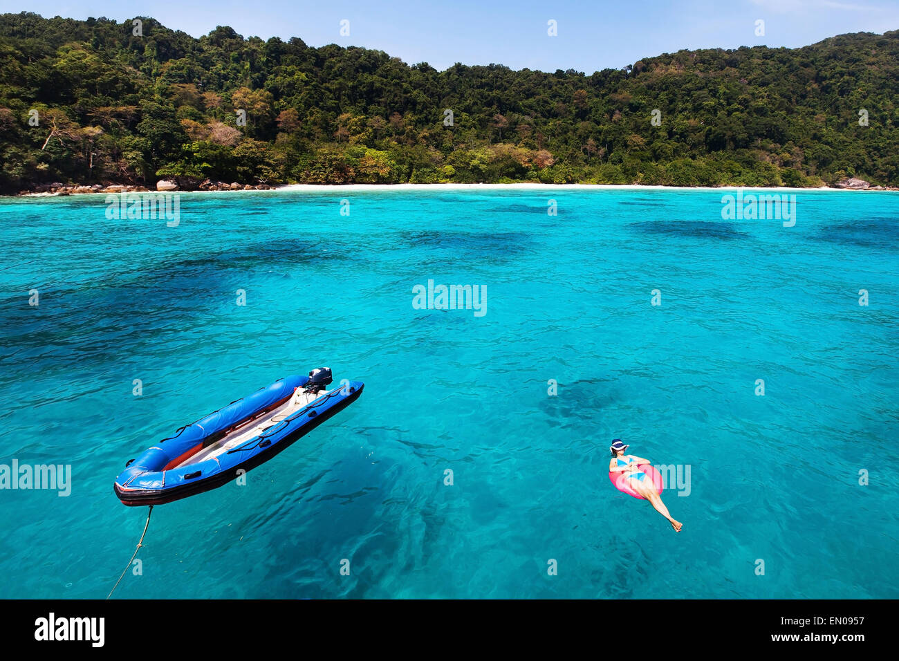 Frau im Bikini entspannend am türkisblauen Strand, Draufsicht Stockbild