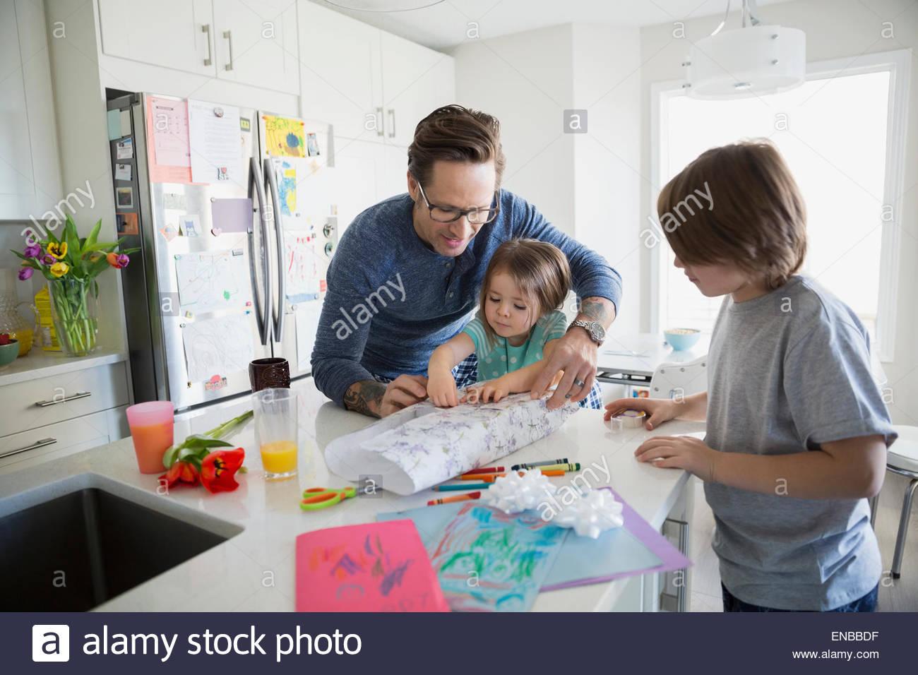 Vater und Kinder wickeln Muttertag Geschenk Küche Stockbild