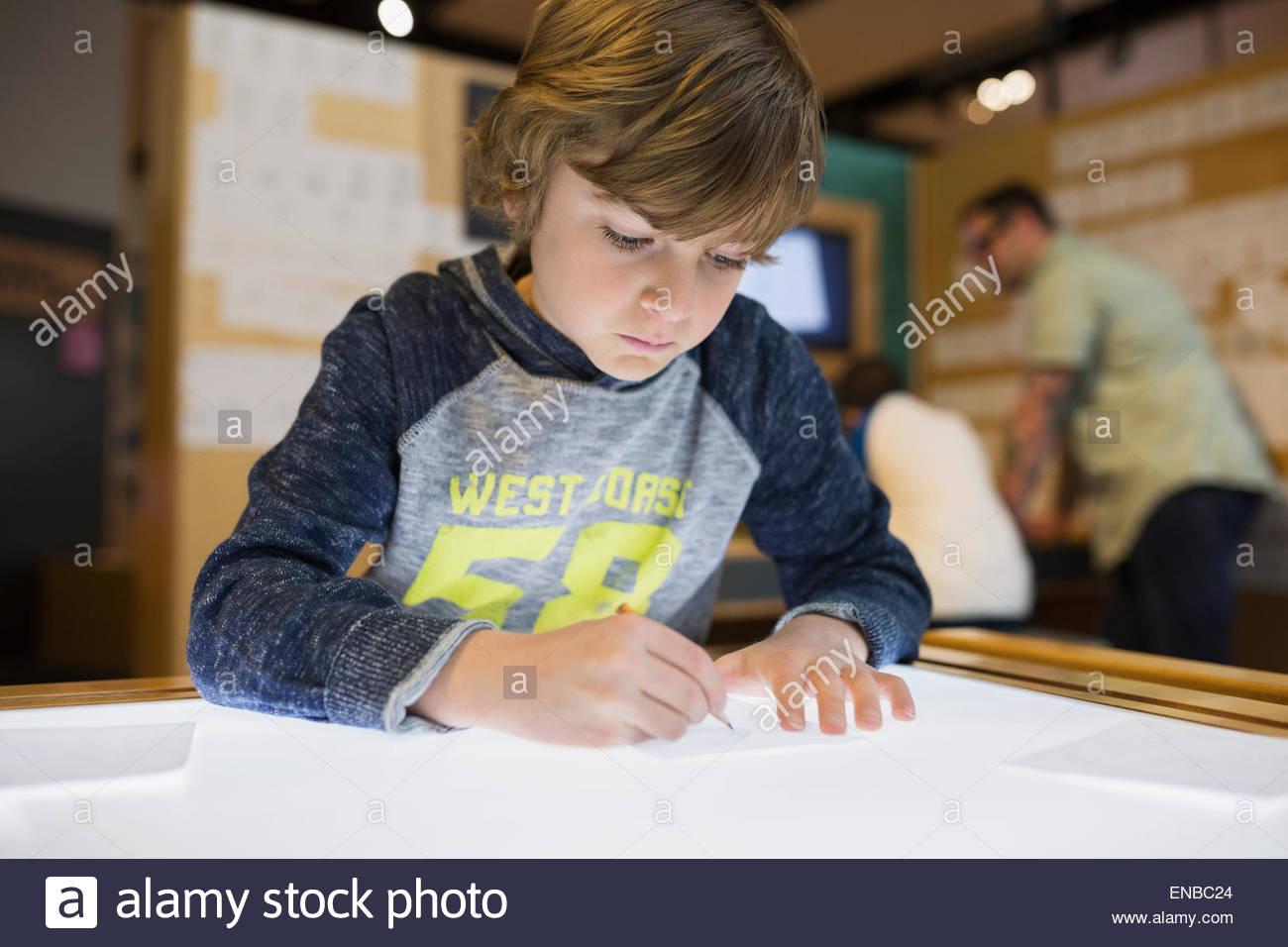 Junge, die Ablaufverfolgung auf Leuchttisch im Science center Stockbild