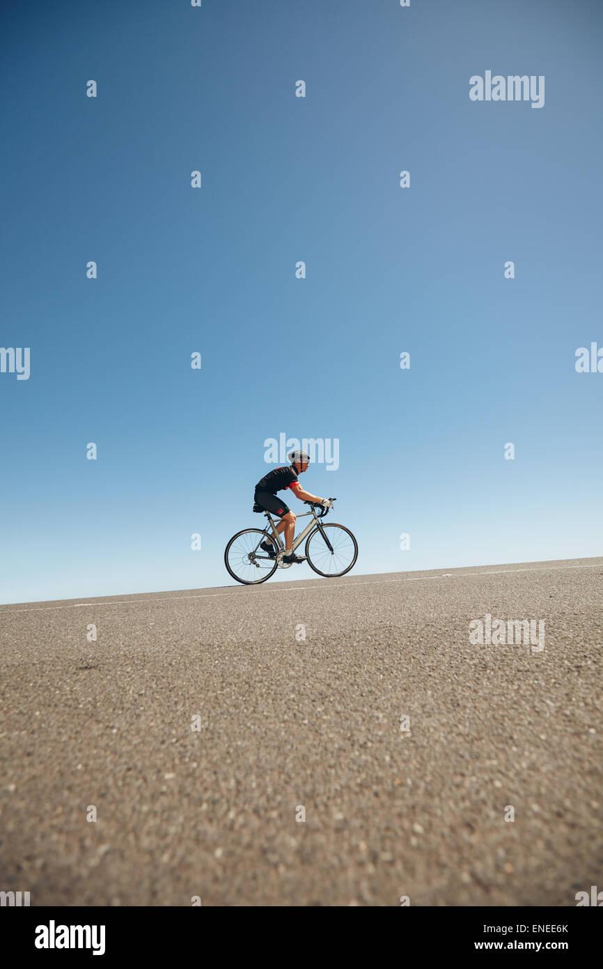 Bild des männlichen Radfahrer fahren Fahrrad bergauf. Sportler, training für Radsport-Event von einem Stockbild