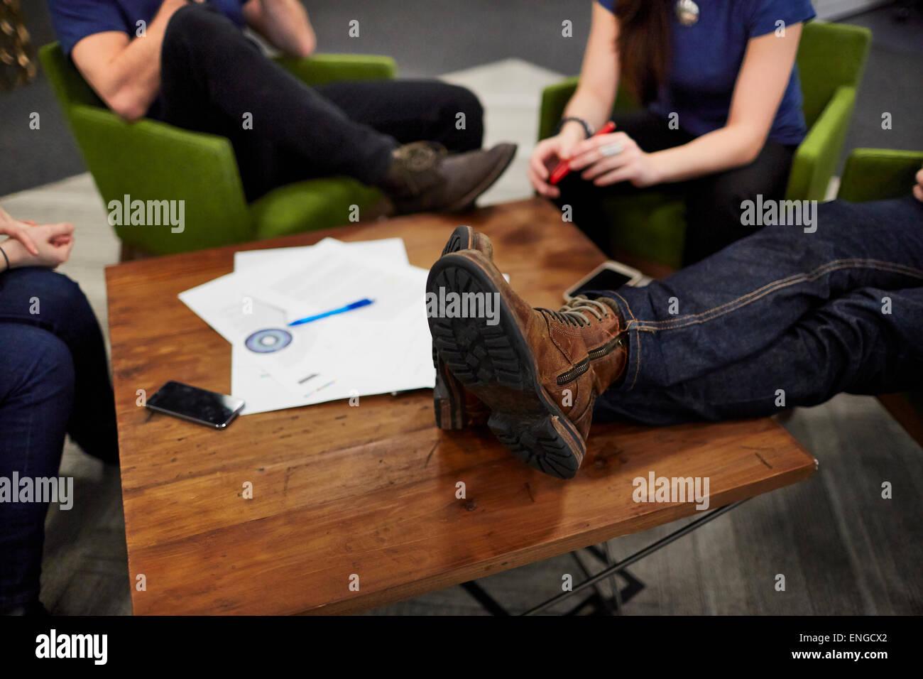 Draufsicht eines Treffens von vier Personen sitzen an einem niedrigen Tisch. Stockbild