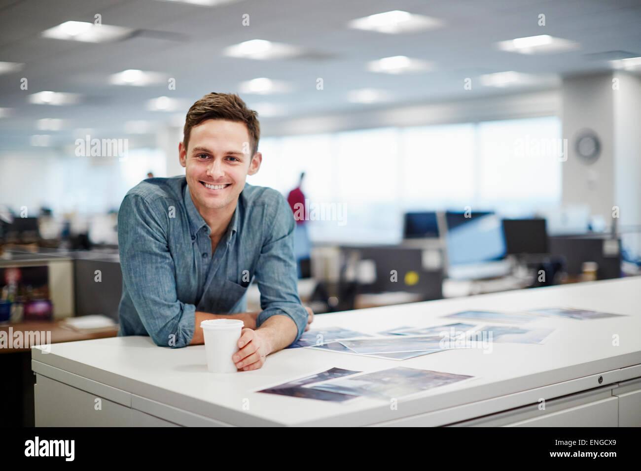 Ein Mann lächelte und beugte sich auf seinem Schreibtisch. Stockbild