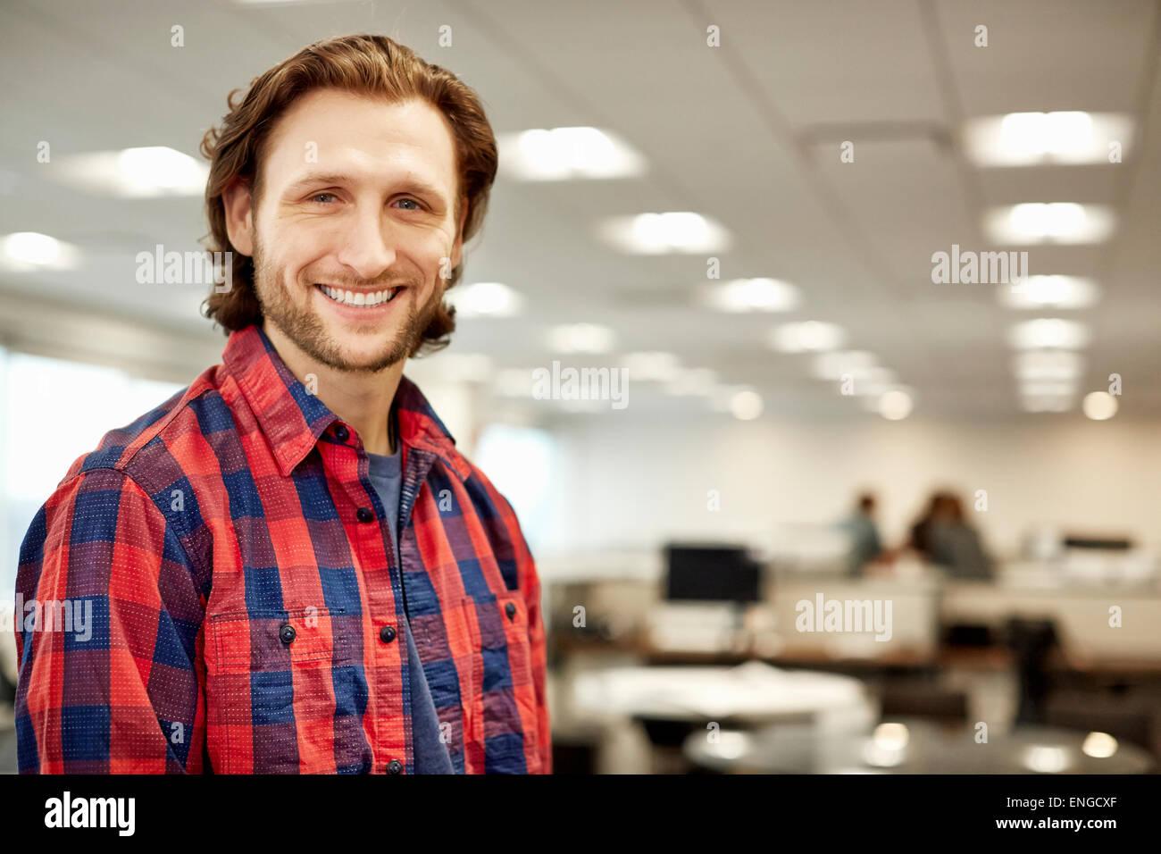 Ein gut aussehender Mann trägt ein kariertes Hemd in einem großen offenen Büro. Stockbild