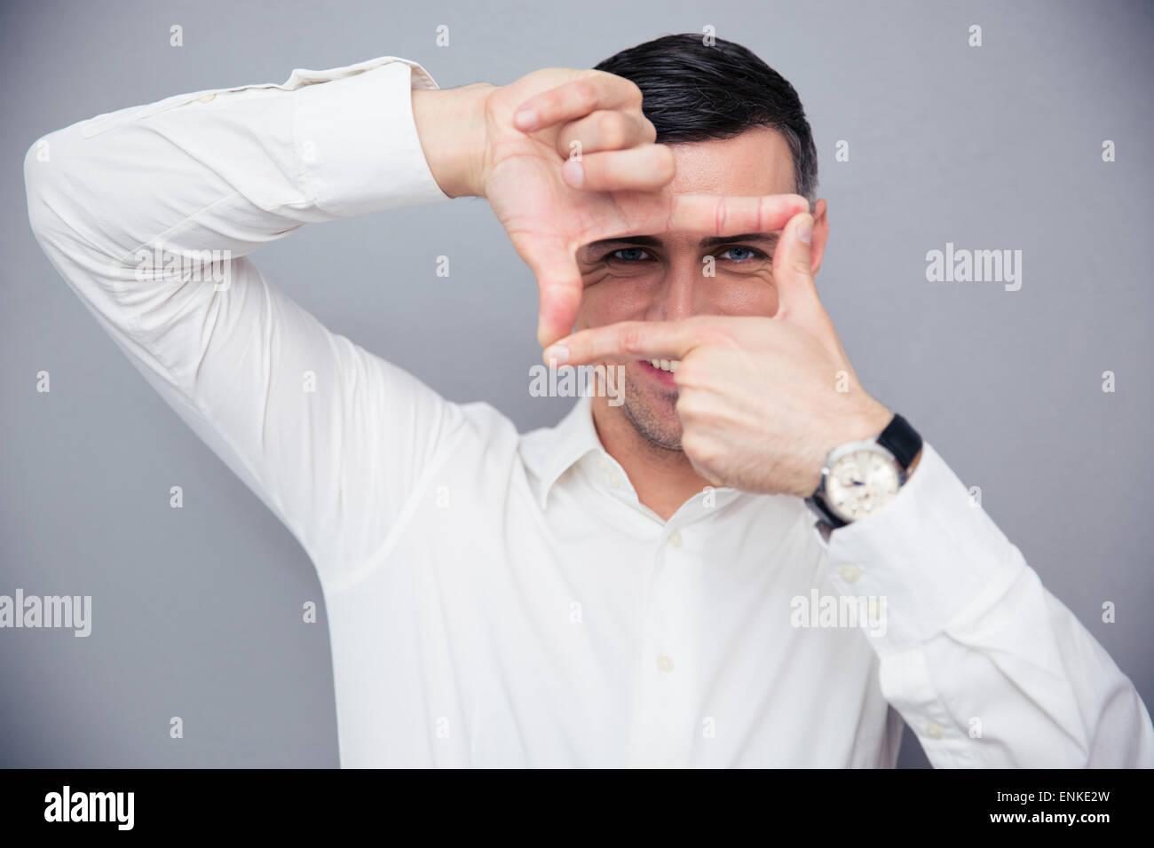 Glücklich Kaufmann macht-Frame mit den Fingern über den grauen Hintergrund und Blick in die Kamera Stockbild