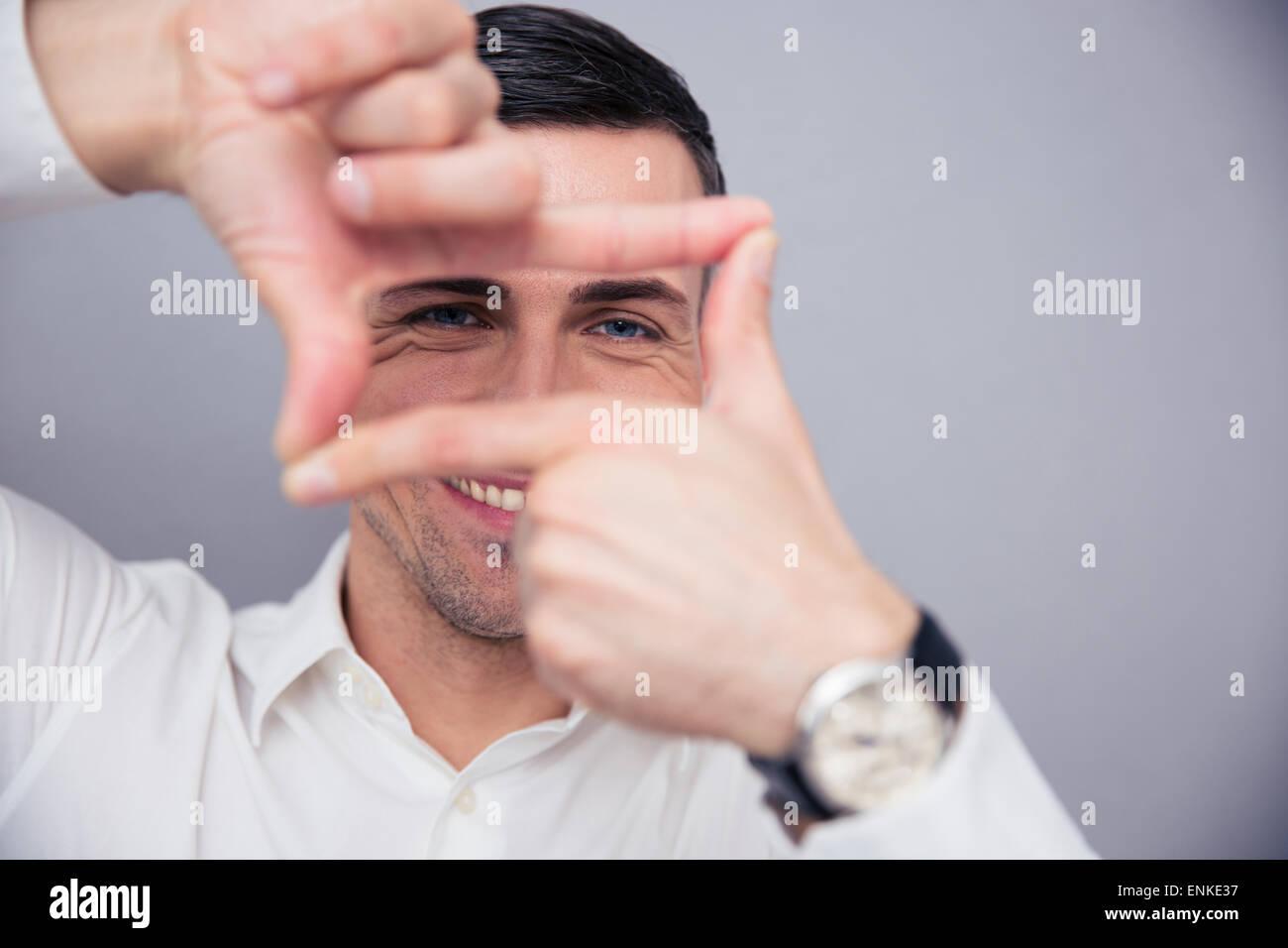 Geschäftsmann macht-Frame mit den Fingern über den grauen Hintergrund und Blick in die Kamera Stockbild
