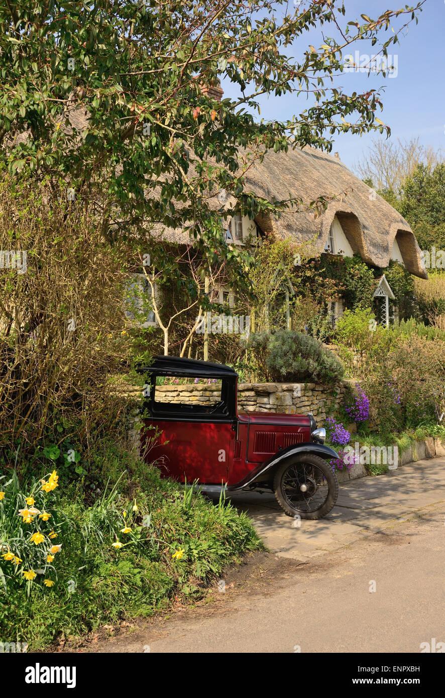 Austin 7 Auto und Reetdachhaus. Stockbild