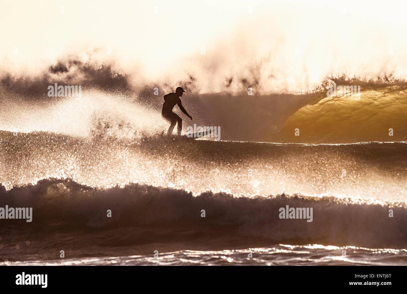 Surfer in schweren Brandung in der Abenddämmerung Stockbild