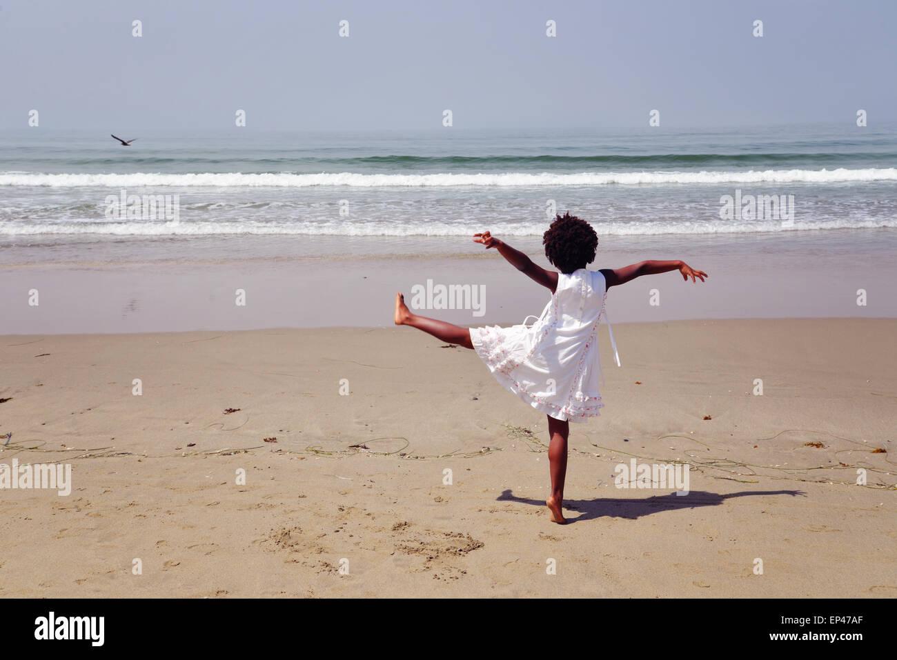 Rückansicht eines afroamerikanischen Mädchen stehen auf einem Bein am Strand Stockbild