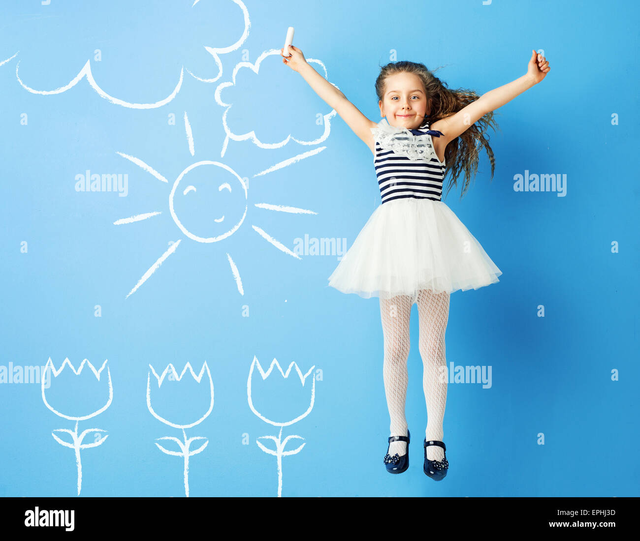 Hübsches Mädchen macht Kreidezeichnungen auf der Wand Stockbild